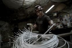 Minero prepara las mechas para la dinamita en una mina en Huanuni